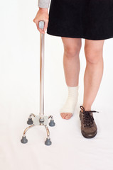 Woman with an injured leg holding a quad stick, isolated