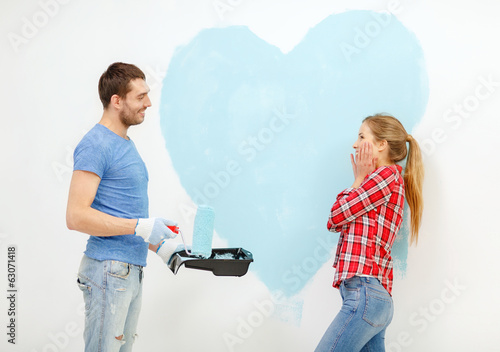 smiling couple painting big heart on wall