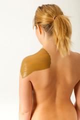 Die junge nackte Frau wird mit Heilerde behandelt
