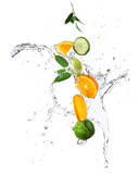 Pieces of oranges and limes in water splash