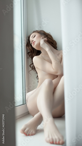 Languid nude model posing lying on windowsill