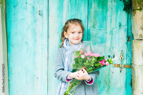 Cute little girl with beautiful bouquet of tiger roses, outdoors