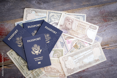 Group of American passports with foreign banknotes