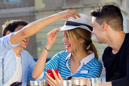 friends having fun with with white hat in the street