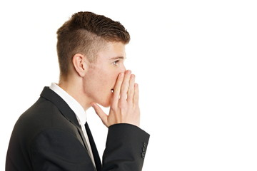 Mman in a suit whispering, with hand he covering mouth