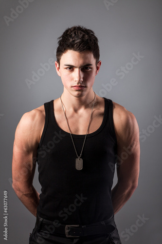 Muscular built man with a dog tags.