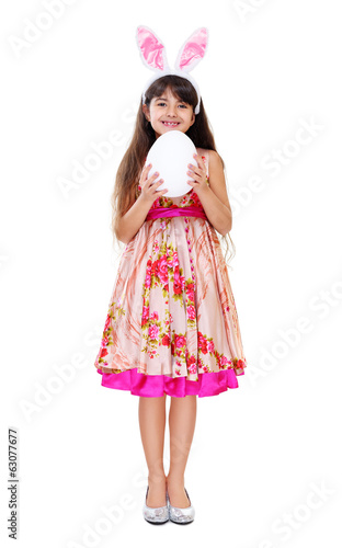 girl wearing bunny ears holding easter egg full length