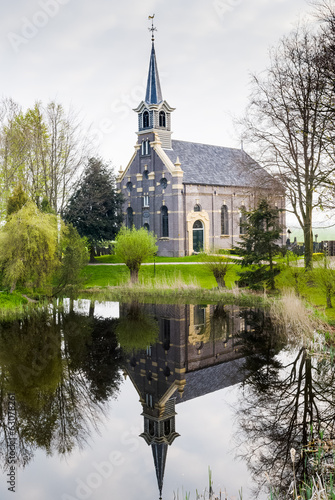 The small church  reflecting in the water in the Netherlands