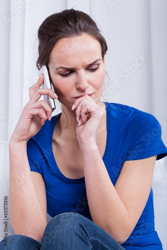 Thoughtful woman talking on the phone