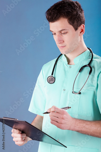 Doctor writing on a clip board