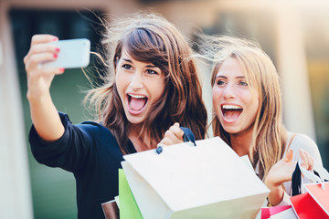"Beautiful girls with shopping bags taking a ""selfie"""
