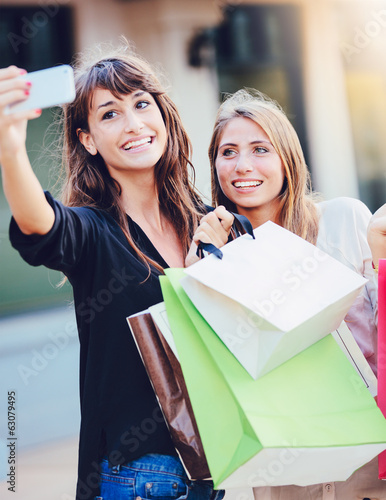 "Beautiful girls with shopping bags taking a ""selfie"""