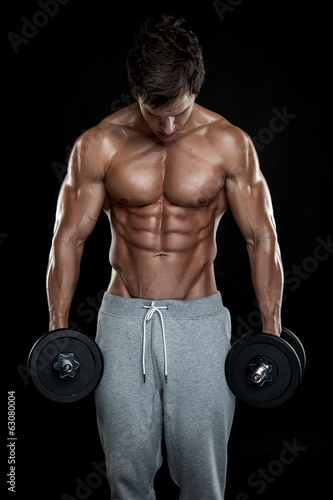 Muscular bodybuilder guy doing exercises with dumbbells over bla