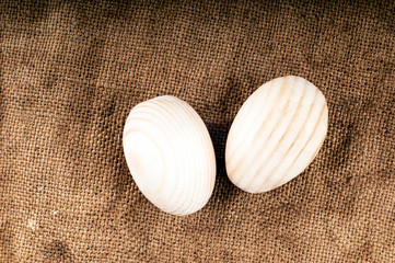 Wooden eggs on sack texture.
