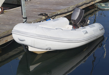 Recreational white rubber raft,outboard motor tied to dock.