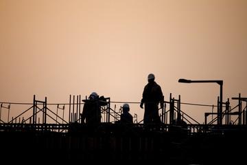 夕日の建築現場で働く人々
