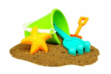 Colorful beach toys in a pile of sand