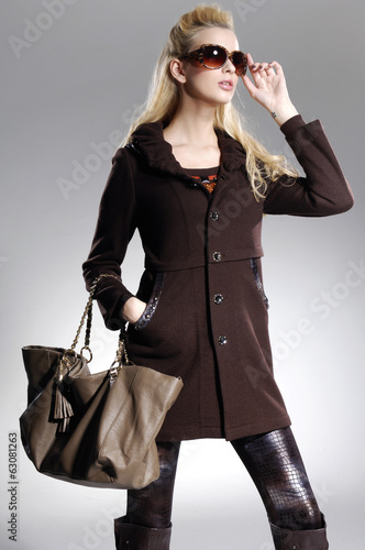 Beautiful Young Model holding bag posing in light background Poster