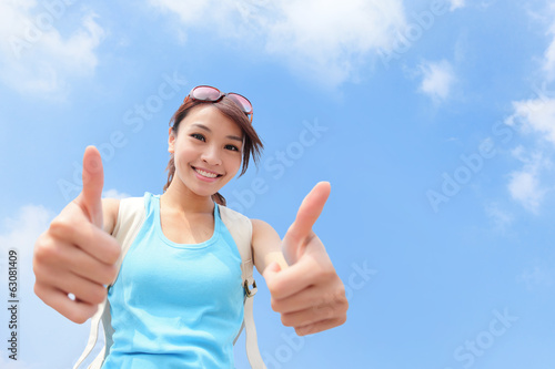 smiling woman tourist showing thumbs up