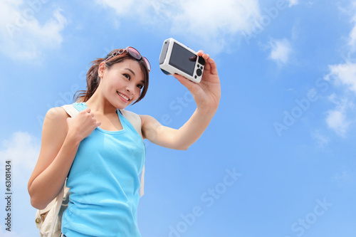 Happy woman traveler photo by camera