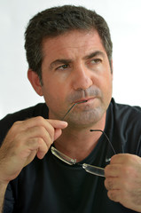 Mature man thinking holding glasses looking away.