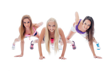 Three charming young sporty girls posing at camera