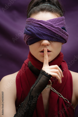 Blindfolded girl finger over lips
