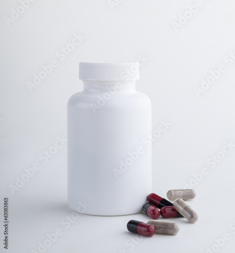 Medicine bottle and tablets isolated on white