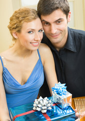 Cheerful amorous couple with gifts, indoors