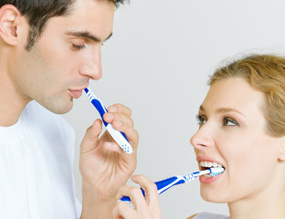 Cheerful young couple cleaning teeth together