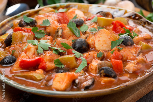 fish stew in tomato sauce on a plate, close-up, selective focus
