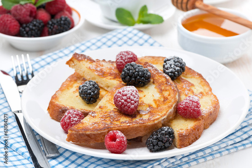 French toast with berries and powdered sugar on a plate