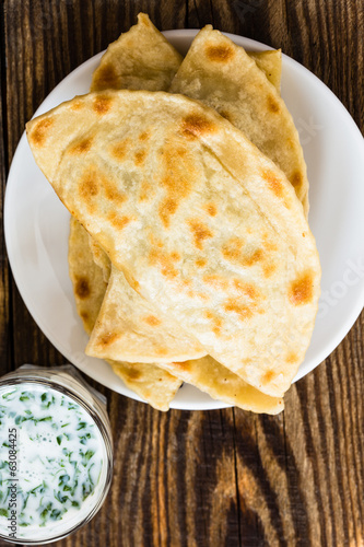 Flat bread on a plate with glass of sour milk viewed from above