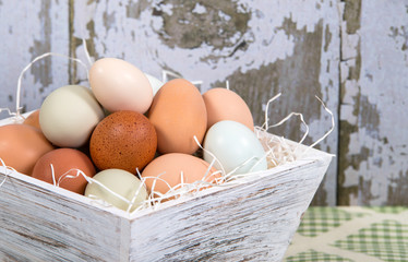 Assortment of fresh eggs in container, country kitchen