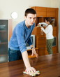 Adult couple dusting wooden furniture