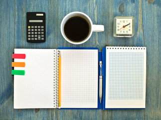 office supplies and checked notebook on wood background