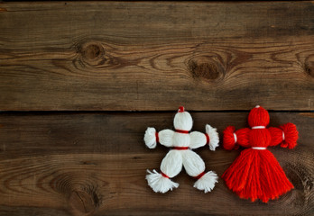 Toys made of red and white threads on a wooden background.