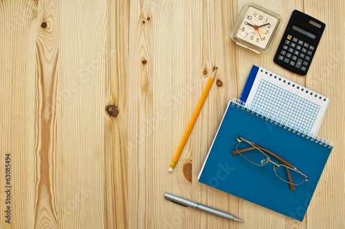 office supplies and glasses on wood background