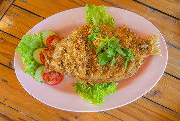 fried tilapia fish with crispy garlic on the table