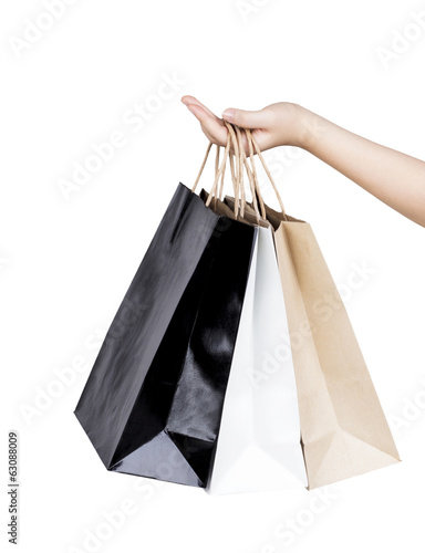 Woman's hand holding paper shopping bags isolated
