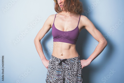 Young woman with toned abs in sports clothing