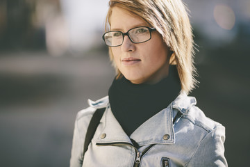 real young woman with glasses going on the street