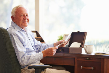 Senior Man Putting Letter Into Keepsake Box