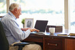 Senior Man Using Laptop On Desk At Home
