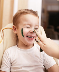 Little boy laughing as his mother paints his face