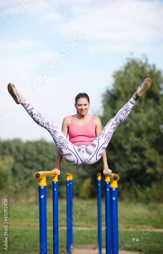 Athletic gymnast exercising on parallel bars