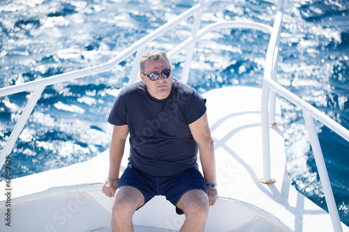 Man sitting on the prow of a boat