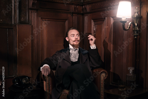 Vintage 1900 fashion man with beard. Sitting in old wooden readi - 63093239