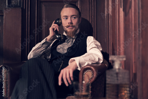 Vintage 1900 fashion man with beard. Sitting in old wooden readi