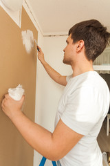Closeup portrait of young man aligning wall with putty